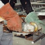 worker with angle grinder cutting steel